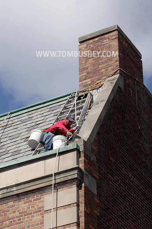 Middletown - A worker repairs the masonary on the roof of a building in downtown Middletown on May 23, 2008.