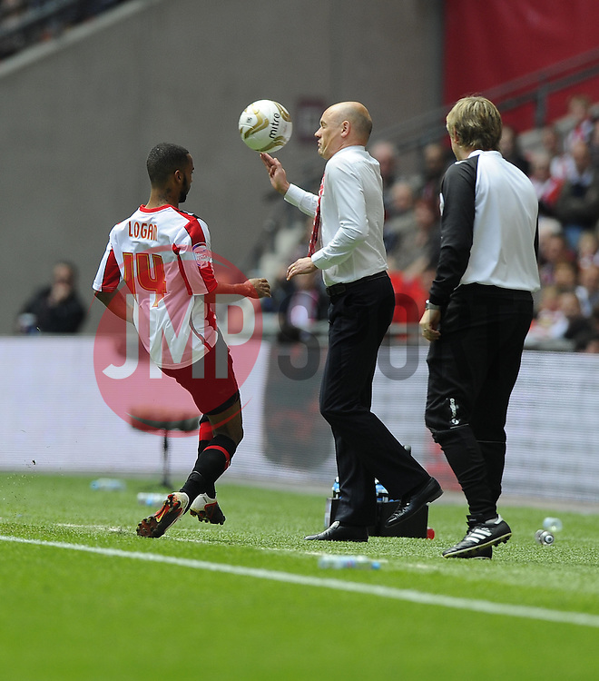 By trying to keep the ball in Brentford's Shaleum Logan kicks the ball in to the face of Brentford's Manger Uwe Rösler - Photo mandatory by-line: Joe Meredith/JMP - Tel: Mobile: 07966 386802 19/05/2013 - SPORT - FOOTBALL - LEAGUE 1 - PLAY OFF - FINAL - Wembley Stadium - London - Brentford V Yeovil Town