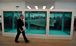 © Licensed to London News Pictures. 02/04/2012. London, UK . People look at 'The Physical Impossibility of Death in the Mind of Someone Living 1991, a 14 ft. shark suspended in formaldehyde. The Tate Modern presents the first substantial retrospective of British artist Damien Hirst. The exhibition tuns 4th April - 9th September at Tate Modern London. Photographers Stephen Simpson/LNP