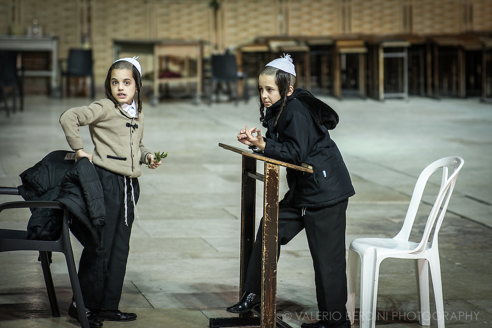 Two children with payot hairstail, kippahs and traditional black orthodox clothes wait at the Western Wall at the end of a Shabbat.