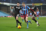 Kevin van Veen of Scunthorpe United under attack from Craig Morgan of Wigan Athletic and Donervon Daniels of Wigan Athletic during the Sky Bet League 1 match between Scunthorpe United and Wigan Athletic at Glanford Park, Scunthorpe, England on 2 January 2016. Photo by Ian Lyall.