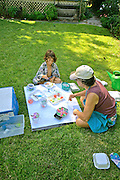 Active Aging Senior Citizens, Retired, Activities, Elderly Woman Paints with Child on Lawn
