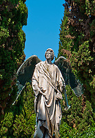 Beautiful, serene scene of a marble and bronze angel set amongst greenery on Isola San Michel in Venice, Italy.