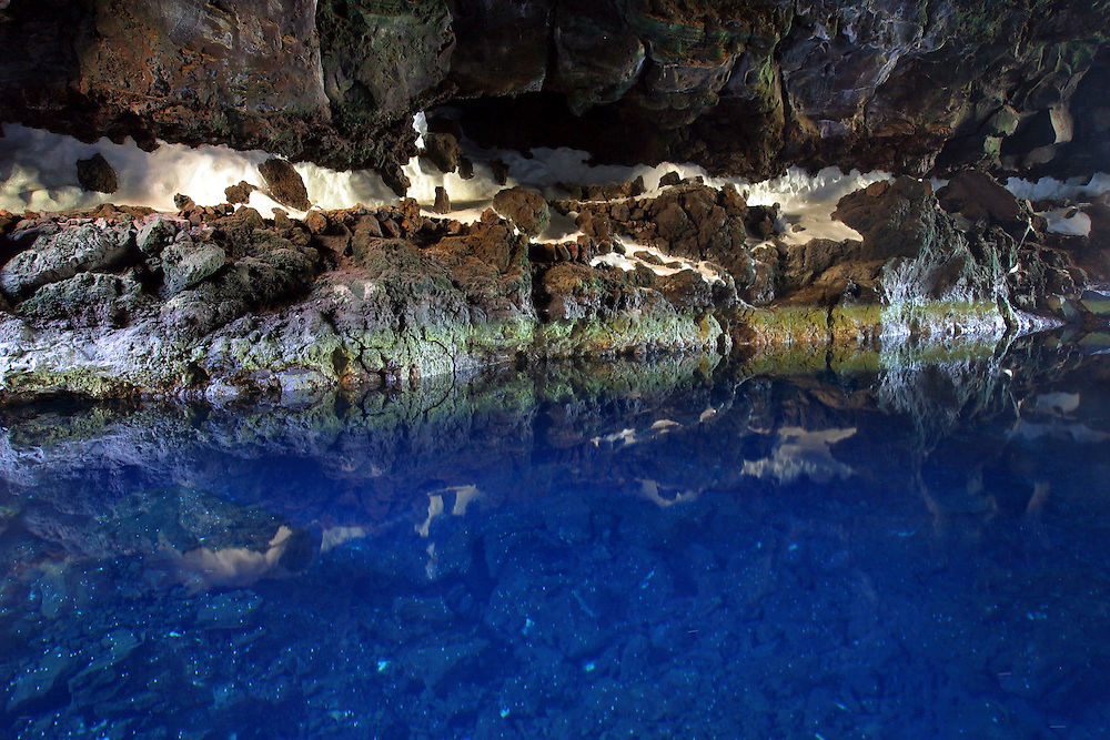 The beautiful blue water in the volcanic cavern of Los Jameos Del Agua in El Malpais de la Corona near the village of Haria, Lanzarote, Spain. It was formed by the lava flow from the eruption of the volcano, La Corona, which advanced while the surface solidified.