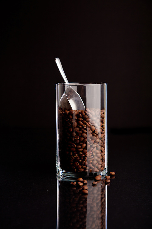 Whole bean coffee in a glass container with an aluminum scoop.