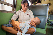 07 JANUARY 2013 - KANCHANABURI, THAILAND:    A woman holds her son in a third class train car on the train between Bangkok (Thonburi station) and Kanchanaburi.  Thailand has a very advanced rail system and trains reach all parts of the country.    PHOTO BY JACK KURTZ