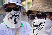 "09 JUNE 2013 - BANGKOK, THAILAND:   A White Mask protester at Central World in Bangkok Sunday. The White Mask protesters wear the Guy Fawkes mask popularized by the movie ""V for Vendetta"" and the protest groups Anonymous and Occupy. Several hundred members of the White Mask movement gathered on the plaza in front of Central World, a large shopping complex at the Ratchaprasong Intersection in Bangkok, to protest against the government of Thai Prime Minister Yingluck Shinawatra. They say that her government is corrupt and is a ""puppet"" of ousted (and exiled) former PM Thaksin Shinawatra. Thaksin is Yingluck's brother. She was elected in 2011 when her brother endorsed her.    PHOTO BY JACK KURTZ"