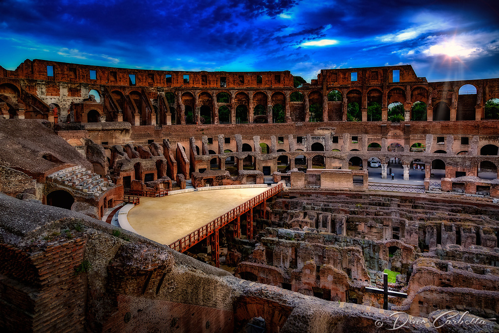 """""""The Cross of the Colosseum illuminated in the evening""""...<br /> <br /> The Colosseum, is an elliptical amphitheatre in the center of the city of Rome, the largest ever built during the Roman Empire. One of the greatest works of Roman architecture and engineering in history, its construction started in 72 AD under the emperor Vespasian and was completed in 80 AD under Titus. Capable of seating 65,000 spectators, it was used for gladiatorial contests and public spectacles. The building ceased to be used for entertainment in the early medieval era. It is one of Rome's most popular tourist attractions and still has close connections with the Roman Catholic Church, as each Good Friday the Pope leads a torch lit """"Way of the Cross"""" procession that starts in the area around the Colosseum. The Colosseum is generally regarded by Christians as a site of the martyrdom of large numbers of believers during the persecution of Christians in the Roman Empire, as evidenced by Church history and tradition. A Cross stands exultant in the Colosseum center with a plaque stating: """"The amphitheatre, one consecrated to triumphs, entertainments, and the impious worship of pagan gods, is now dedicated to the sufferings of the martyrs purified from impious superstitions."""" In viewing many historical sites during my journey in Italy, seeing the iconic Colosseum for the first time…I became awestruck. It is as grand in person as it appears in the media, and it seems to hold a very mystical aura. Climbing the ancient steps inside, one cannot help but feel not only the suffering of its past, but the forgiveness and sacrifice of its present stature. As evening descended on the ancient Colosseum, the sun illuminated the cross. I was determined to capture this amazing image as the security guards circled to kick me out..."""