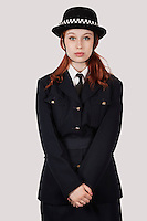 Portrait of young woman in police officer's costume standing against gray background