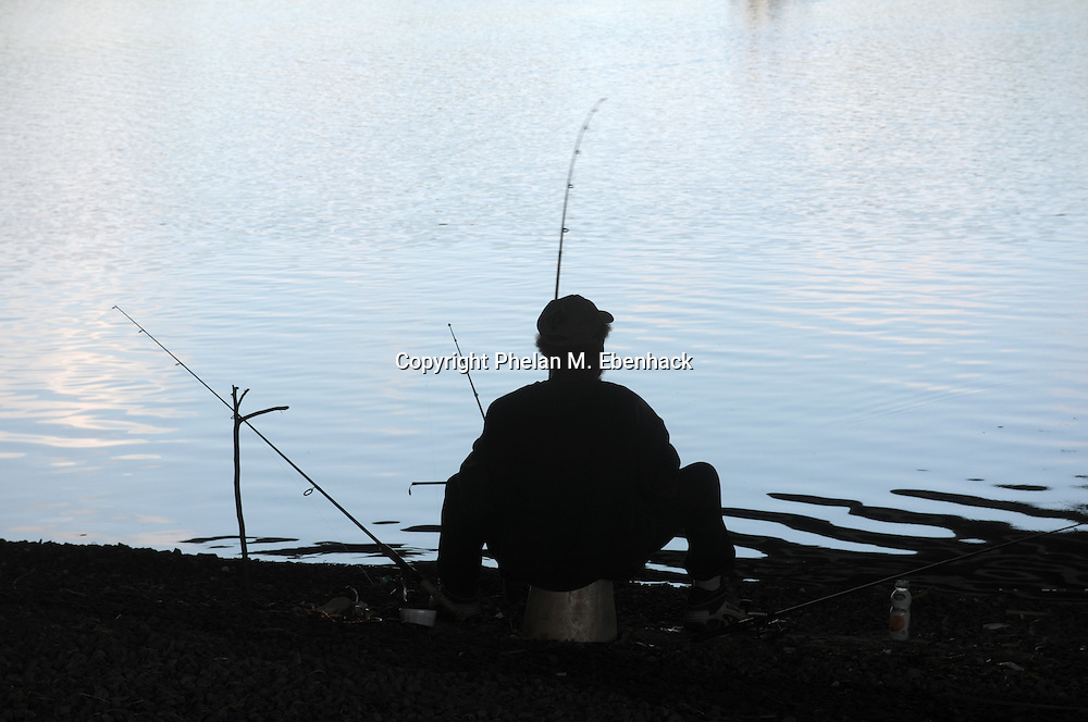 A fisherman watches his lines while fishing on a lake in Orlando, Florida, Thursday, Oct. 2, 2008.