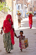 Indian woman shopping with child in the village of Narlai in Rajasthan, Northern India