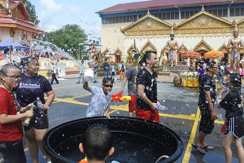 A child throwing water from a container at the Songkran water festival