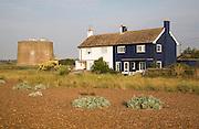 Martello tower and beach houses at coastal hamlet of Shingle Street, North Sea coast, Suffolk, England, UK