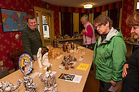 Rev. John Eaton talks to Ginny Timmons, Lee Stecher and Suzanne Larson about his nativity scenes from around the world displayed at the Meredith Bay Colony Club through Sunday.  (Karen Bobotas/for the Laconia Daily Sun)
