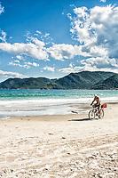 Homem andando de bicicleta na Praia do Pântano do Sul. Florianópolis, Santa Catarina, Brasil. / <br /> Man riding a bike at Pantano do Sul Beach. Florianopolis, Santa Catarina, Brazil.