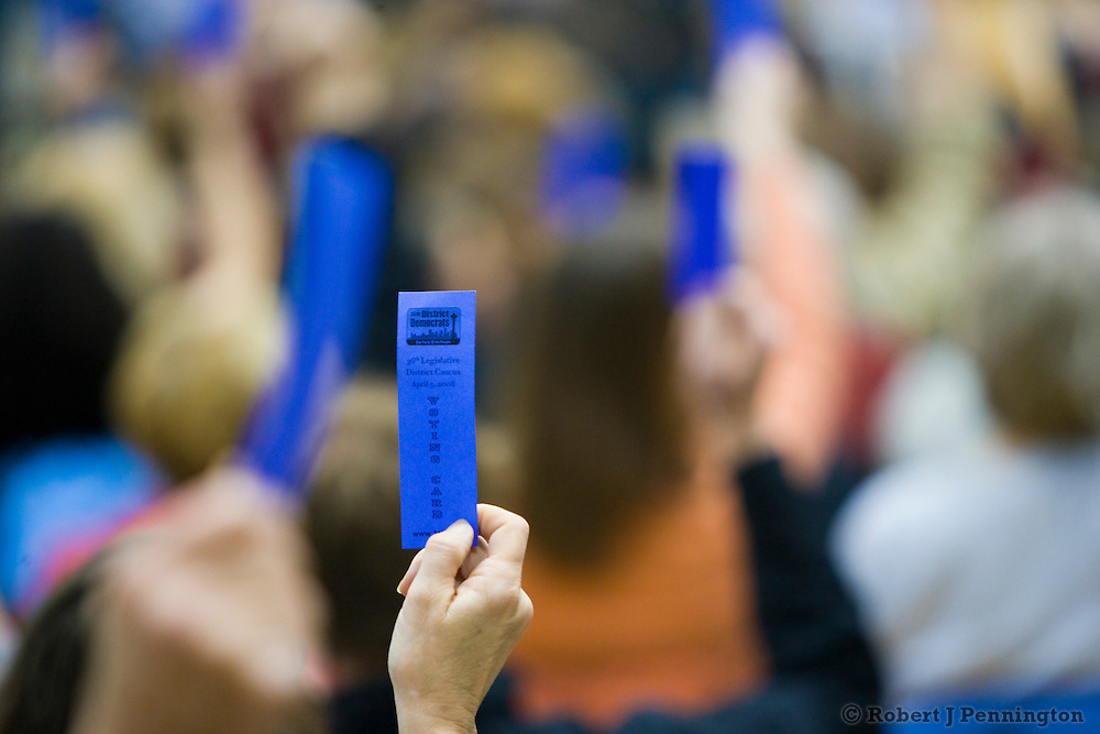 Hands are raised and blue tickets are counted at a local Seattle, WA democratic caucus