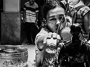 "11 APRIL 2017 - BANGKOK, THAILAND: A woman bathes a statue of the Buddha in scented water during the Songkran travel period at Hua Lamphong train station in Bangkok. Songkran is the traditional Thai Lunar New Year. It is celebrated, under different names, in Thailand, Myanmar, Laos, Cambodia and some parts of Vietnam and China. In most places the holiday is marked by water throwing and water fights and it is sometimes called the ""water festival."" This year's Songkran celebration in Thailand will be more subdued than usual because Thais are still mourning the October 2016 death of their revered Late King, Bhumibol Adulyadej. Songkran is officially a three day holiday, April 13-15, but is frequently celebrated for a full week. Thais start traveling back to their home provinces over the weekend; busses and trains going out of town have been packed.     PHOTO BY JACK KURTZ"