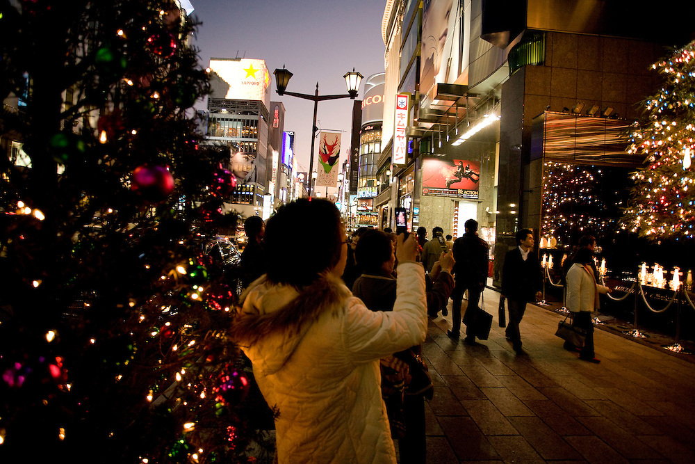 Shoppers using cell phones to photograph  Christmas lights in Tokyo's Ginza district..Monk collecting money stands in front of store, Holiday windowdisplay