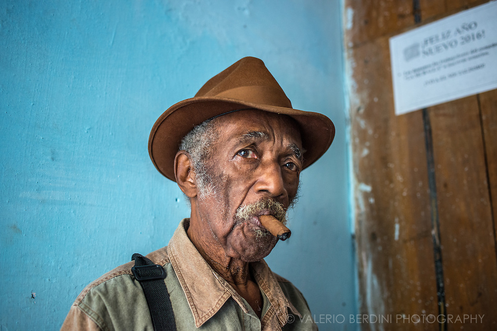 A man puffs a cigar while waits for his turn at a social centre for elderly people. Havana, Cuba