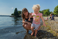 United States, Washington, Kirkland, Mother and baby girl playing at waterfront on Lake Washington.  MR