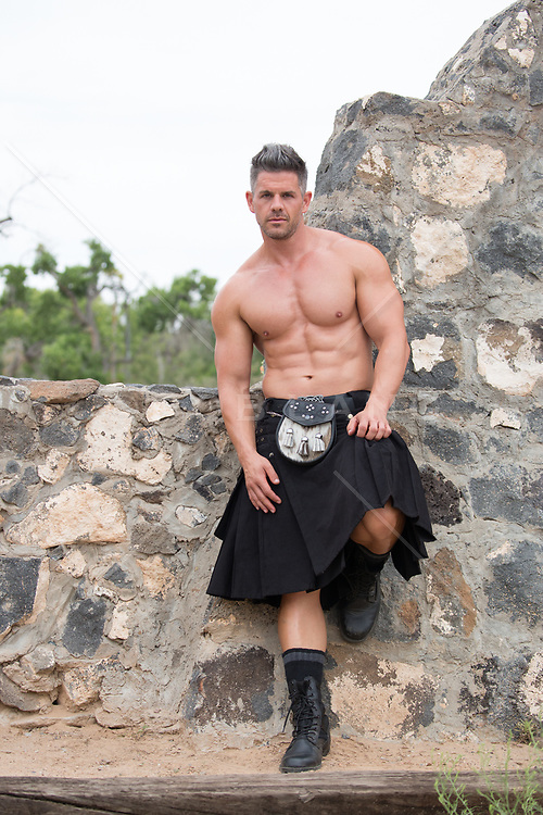shirtless muscular man in a kilt by a stone wall