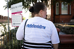 "© Licensed to London News Pictures. 19/07/2018. Salford, UK. A protester wearing a t-shirt with "" We believe in drew "" on the back . Harrop Fold School in Little Hulton is closed for a protest by parents , objecting to the outcome of a months-long investigation in to record keeping which, it is alleged, revealed that data relating to pupils' performance was embellished and which has seen the school's popular headmaster suspended from duty. Parents planned a protest following the suspension of head master Drew Povey alongside three other members of staff . The school , which has been featured in the documentary "" Educating Greater Manchester "" will remain closed throughout the day . Photo credit: Joel Goodman/LNP"