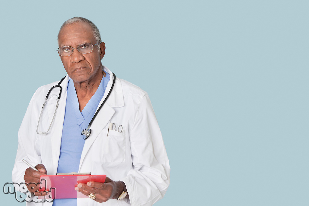 Portrait of an African American senior doctor holding clipboard over light blue background