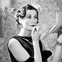 A woman fixes her lipstick at a wedding in Barcelona, Spain.  The wedding had a 1940´s theme