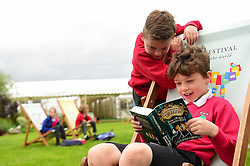 © London News Pictures. 26/05/2016. Hay on Wye, UK. The opening day of the Hay Festival 2016, and two young pupils from local schools read one of the books they've bought from the festival bookshop. Photo credit: Keith Morris/LNP