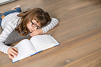 High angle view of teenage girl sleeping while studying on floor