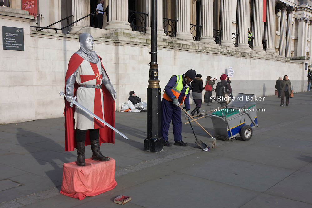 A street busker dressed as a crusader stands silent and motionless outside the National Portrait Gallery in Trafalgar Sq.