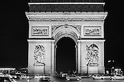 Cars circling the Arc de Triomphe  against a dark night sky. The monument stands at the centre of the Place Charles de Gaulle at the western end of the Champs-Élysées. The Arc de Triomphe is one of the most famous monuments in Paris.