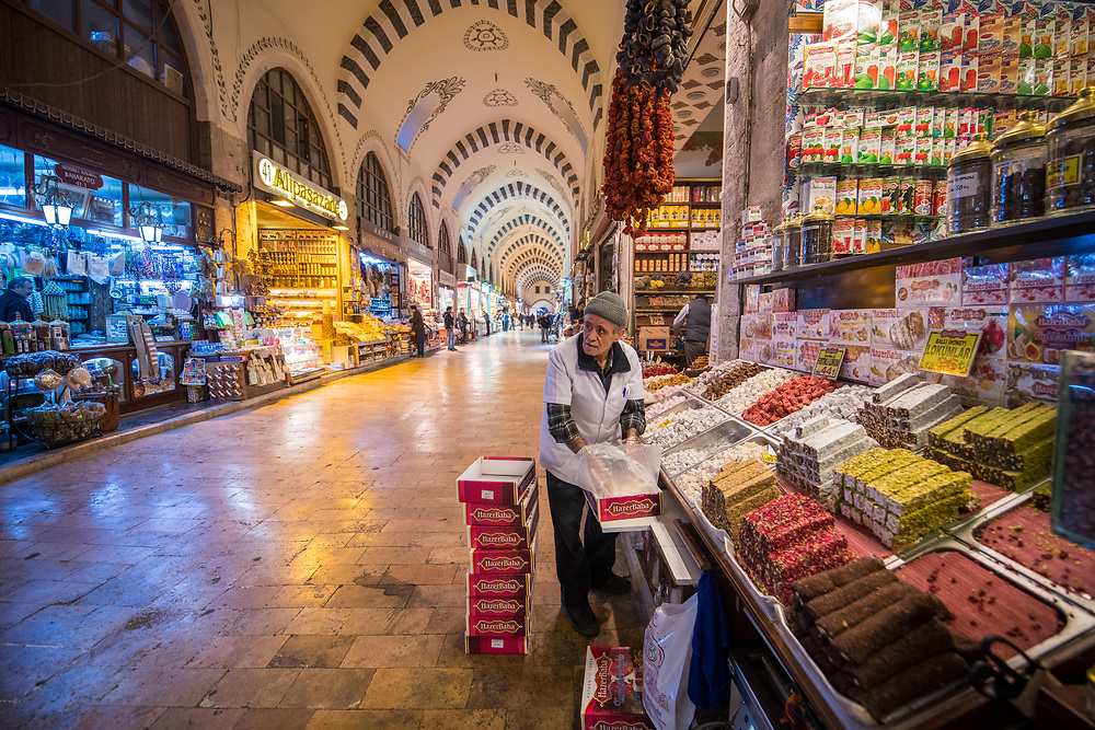 Male merchant restocking the display of Turkish delights at this market stall in Istanbul Spice bazaar in Turkey