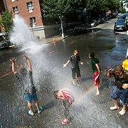 July 2, 2014 - New York, NY : <br /> Kids play in the water of an open fire hydrant at the corner of East Clarke Pl. and Walton Ave. in the Bronx on Wednesday afternoon.<br /> CREDIT: Karsten Moran for The New York Times