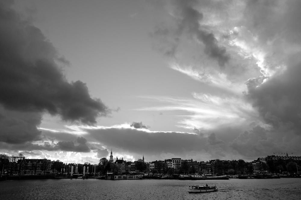 Boat crosses the Oosterdok in Amsterdam under cloudy autumn skies.
