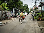 20 JULY 2015 - NONTHABURI, NONTHABURI, THAILAND:  A pedicab in the town of Nonthaburi, a suburb north of Bangkok. Nonthaburi is the northern end of the Chao Phraya River redevelopment project. The Chao Phraya promenade is development project of parks, walkways and recreational areas on the Chao Phraya River between Pin Klao and Phra Nang Klao Bridges. The 14 kilometer long promenade will cost approximately 14 billion Baht (407 million US Dollars). The project involves the forced eviction of more than 200 communities of people who live along the river, a dozen riverfront  temples, several schools, and privately-owned piers on both sides of the Chao Phraya River. Construction is scheduled on the project is scheduled to start in early 2016. There has been very little public input on the planned redevelopment.          PHOTO BY JACK KURTZ