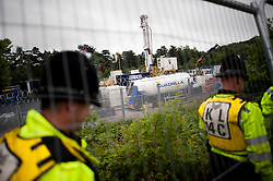 © London News Pictures. 16/08/2013. Balcombe, UK. Police guard the perimeter to the Cuadrilla drilling site in Balcombe, West Sussex which has been earmarked for fracking. Cuadrilla has temporarily ceased drilling at the site under advice from the police after campaign group No Dash For Gas threatened a weekend of civil disobedience. Photo credit: Ben Cawthra/LNP