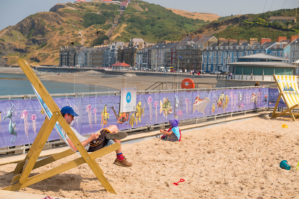 © Licensed to London News Pictures. 05/07/2018. Aberystwyth, UK. A man relaxes in a giant deckchair on  the beach at mid-morning  in Aberystwyth at the start of what promises to be yet another hot and almost cloudless day, as the prolonged heatwave continues to dominate the weather over the UK. Photo credit Keith Morris/LNP