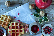 Christmas table for breakfast with golden fresh baked waffle topped with pomegranate sorbet.