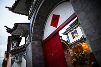 An overview of the home of artist Ye Yongqing in Dali, China, as seen from the main entryway, through the red doors on the street.