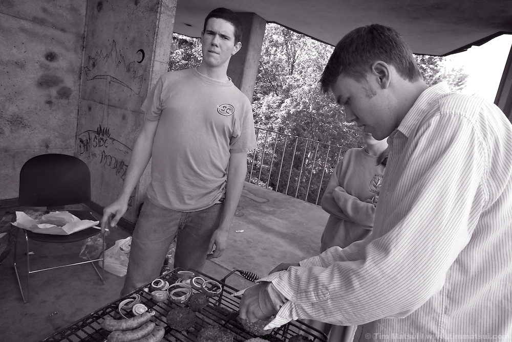 Tom smokes while Andy manages the grill outside their dorm early in an evening of end-of-the-year partying.