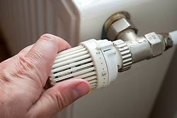 Man turning down thermostat on gas powered central heating radiator to save energy