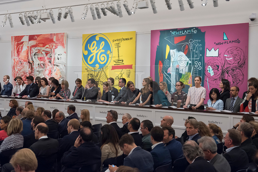 """© Licensed to London News Pictures. 28/06/2017. London, UK. Sotheby's staff bid on behalf of telephone clients in front of (L to R) """"The Girl Who Had Everything"""", 1998, by Cecily Brown sold for a hammer price of GBP1.55m (estimate GBP0.8-1.2m), """"Sweet Pungent"""", 1984-85, a collaborative work by Andy Warhol and Jean-Michael Basquiat sold for a hammer price of GBP3.8 m (estimate GBP1.4-1.8m) and """"New Flame"""", 1985, a collaborative work by Andy Warhol and Jean-Michael Basquiat sold for a hammer price of GBP2m (estimate GBP1.7-2.2m) at Sotheby's Contemporary Art evening sale in New Bond Street, which featured pioneering works from the Pop Art genre. Photo credit : Stephen Chung/LNP"""