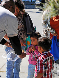 A volunteer gives out cookies to those waiting in line at St. Clare's Corner, established in Salinas by the Franciscan Workers of Junipero Serra in 1982. Supplied by the Food Bank of Monterey County, basic foodstuffs like rice and beans supplement family diets from October to May, the winter months when unemployment is highest.