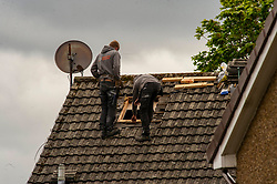 Two builders work closely to fit a Velux window.  <br /> While larger construction companies may be able to return to work with social distancing, it will be hard for smaller firms to comply when only two people working on a job.