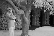 A man talking on his cell phone while watching the Thoroughbreds prior to a race at Keeneland Race Course, Lexington, KY.  Infrared (IR) photograph by fine art photographer Michael Kloth. Black and white infrared photographs