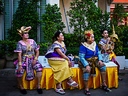 "03 NOVEMBER 2017 - BANGKOK, THAILAND: Traditional Thai dancers relax backstage during Loi Krathong at Wat Prayurawongsawat on the Thonburi side of the Chao Phraya River. Loi Krathong is translated as ""to float (Loi) a basket (Krathong)"", and comes from the tradition of making krathong or buoyant, decorated baskets, which are then floated on a river to make merit. On the night of the full moon of the 12th lunar month (usually November), Thais launch their krathong on a river, canal or a pond, making a wish as they do so. Loi Krathong is also celebrated in other Theravada Buddhist countries like Myanmar, where it is called the Tazaungdaing Festival, and Cambodia, where it is called Bon Om Tuk.     PHOTO BY JACK KURTZ"
