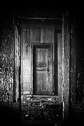 a dilapidated door of an abandoned rumah gadang where its solitude is slowly destroying it from the inside.