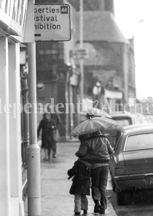 People captured in the rain in the Liberites in Dublin, May 14 1975. <br /> (Part of the Independent Ireland Newspapers/NLI Collection)