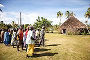 Entrée d'un clan de la tribu de Xodre à l'intérieur de la tribu de Huiwatrul par voie coutumière détournée.<br /> Afin de rejoindre le clan de l'homme et de sceller les liens du mariage, le clan de la femme doit suivre les chemins coutumiers intergénérationnels. Une « grand-mère » du clan avait ouvert cette voie deux générations auparavant en se mariant avec un homme de cette tribu. De ce fait, la voie directe est impossible pour rejoindre le clan de l'homme. Le clan de la femme doit procéder à une étape en suivant le chemin de cette première union, dont la descendance devient le porteur de la Parole.<br /> Cérémonie coutumière de mariage – Huiwatrul, grande chefferie de Lössi, Lifou, Îles Loyauté, Nouvelle-Calédonie - Avril 2014